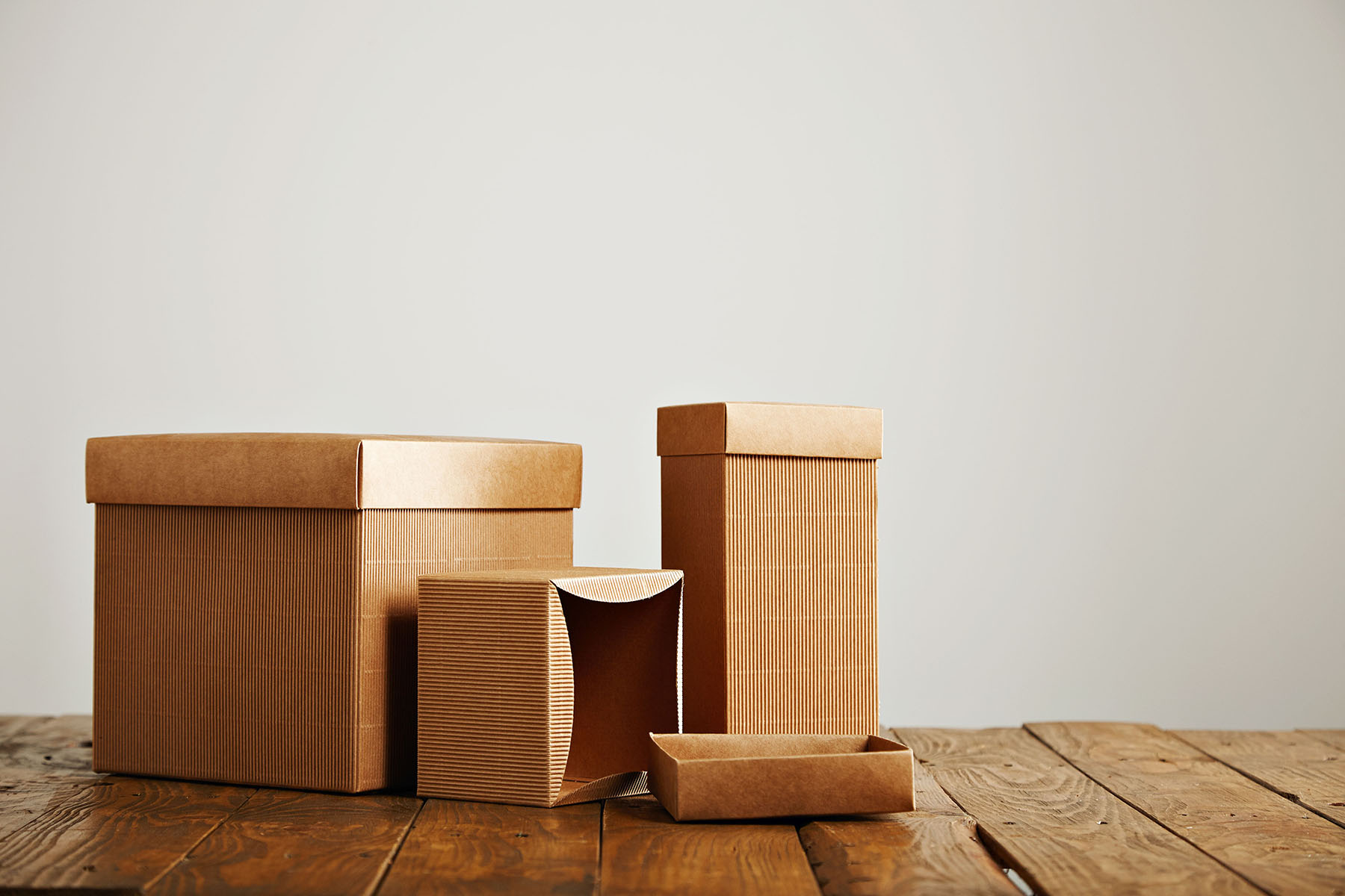 Unlabeled similar boxes of different shapes and sizes on an uneven wooden table isolated on white
